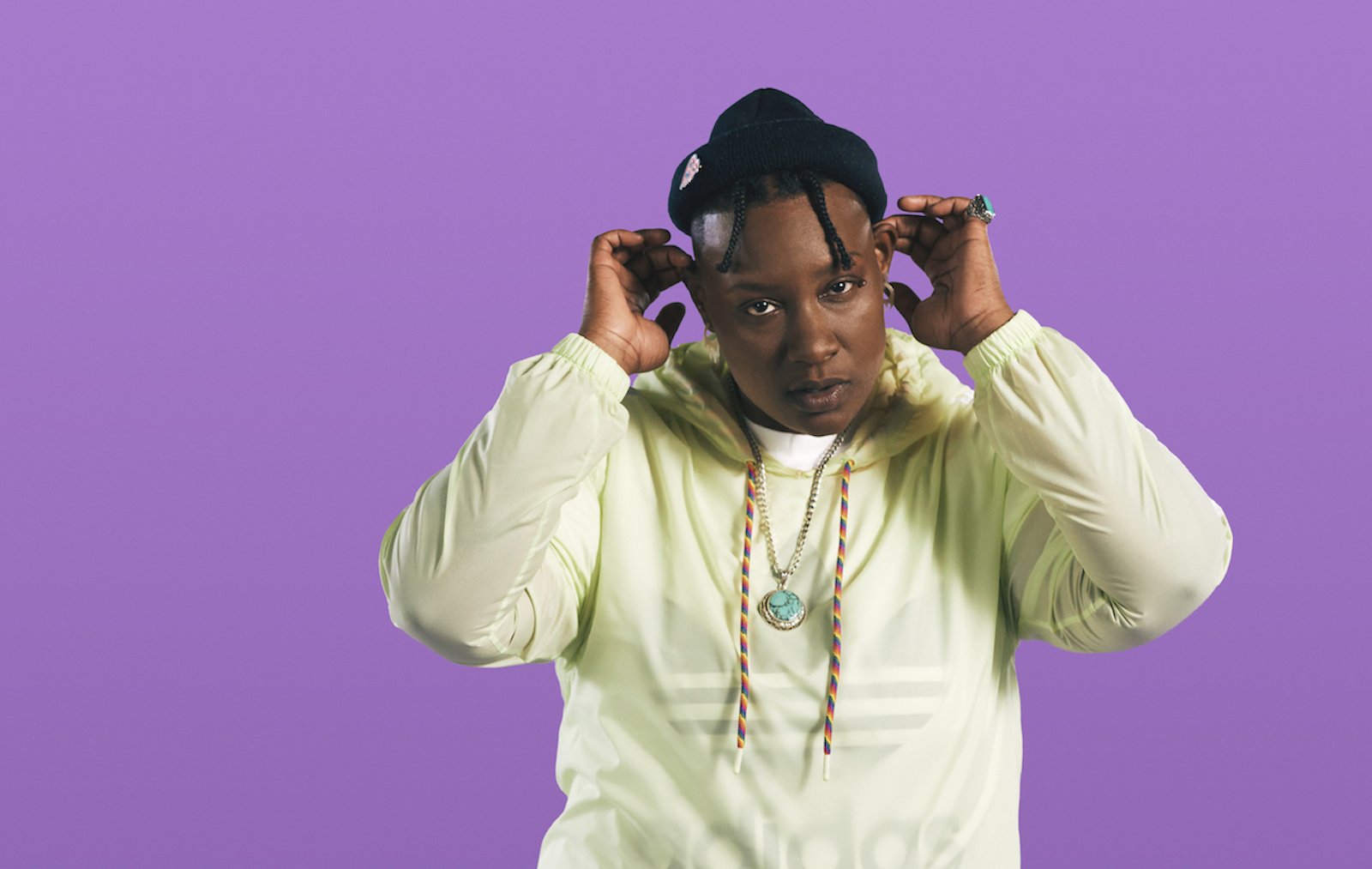 A portrait of the Last Artful, Dodgr, wearing a yellow hoodie, against a purple background.