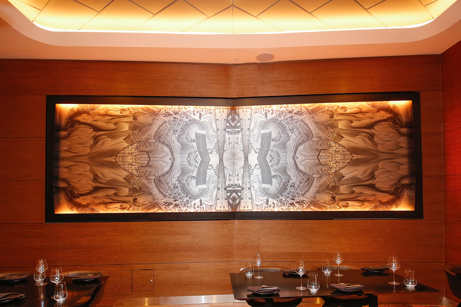 Lightbox mural of an abstracted and mirrored aerial topographical view displayed on a gently angled wood paneled wall behind set tables in the restaurant.