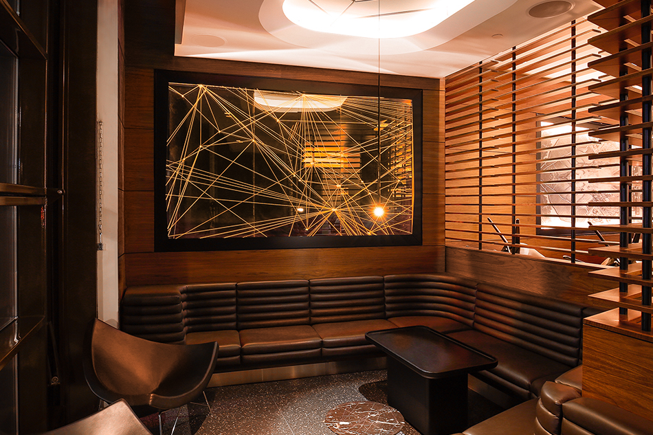 Illuminated flight paths over a dark panel on a wall above a leather and wood booth.