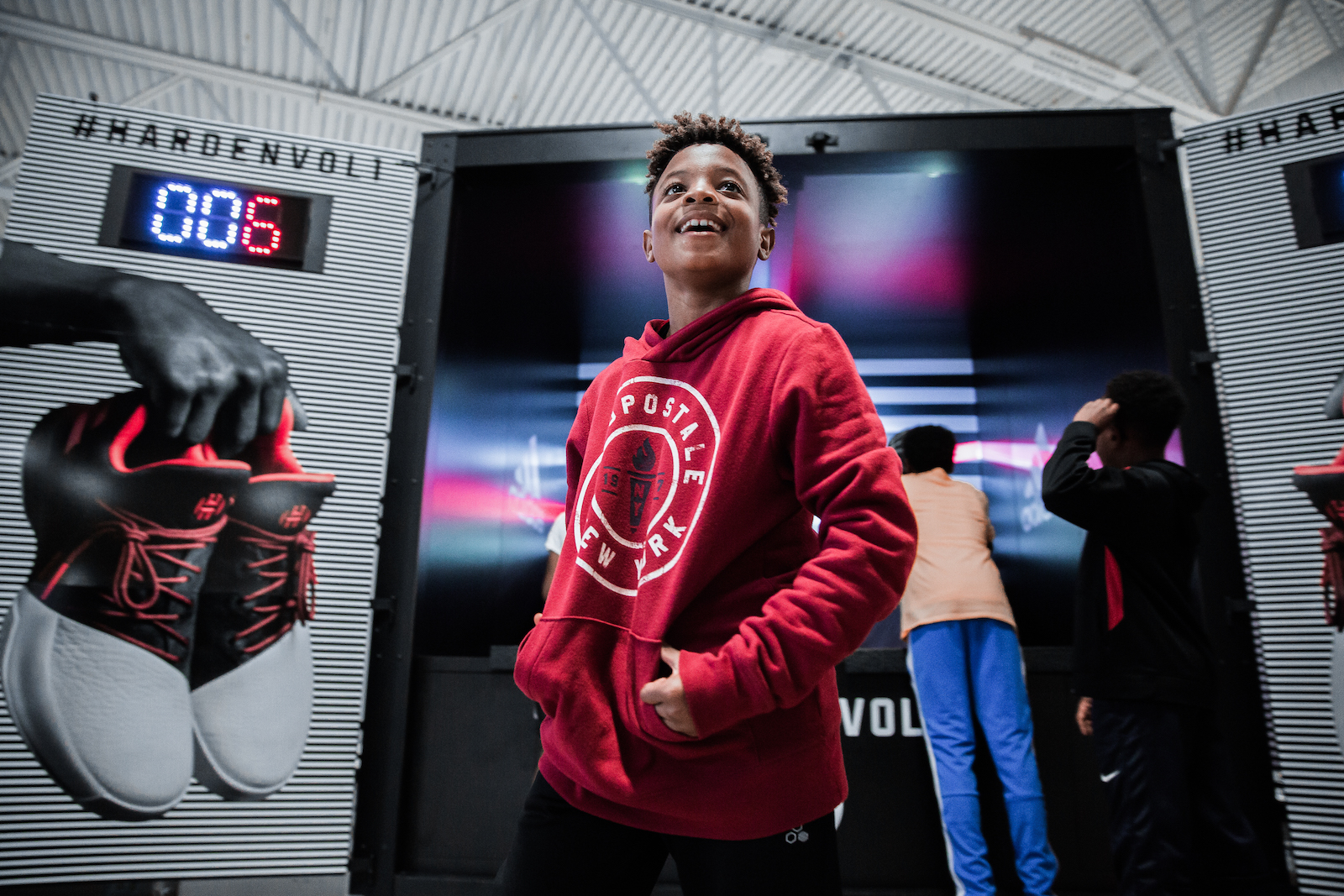 A smiling kid stands in front of the pop-a-shot game while two other kids play behind him.