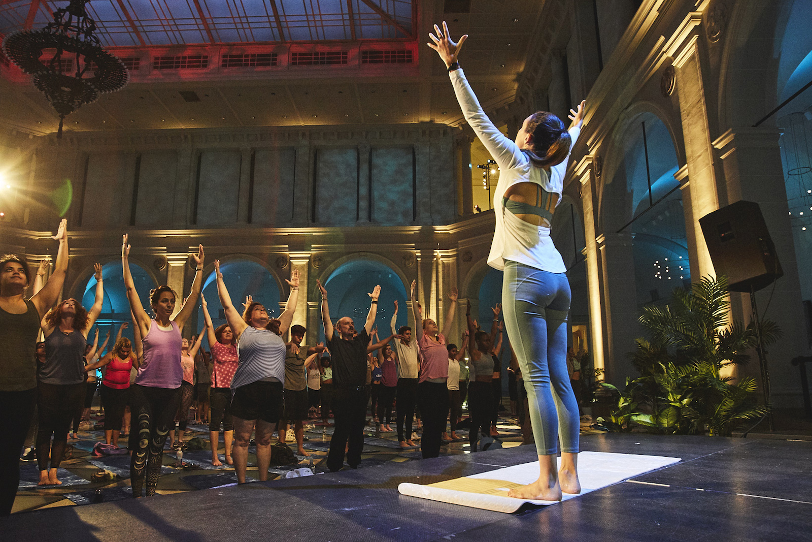 People stand with arms raised as they do yoga together, led by an instructor, in the Brooklyn Museum.