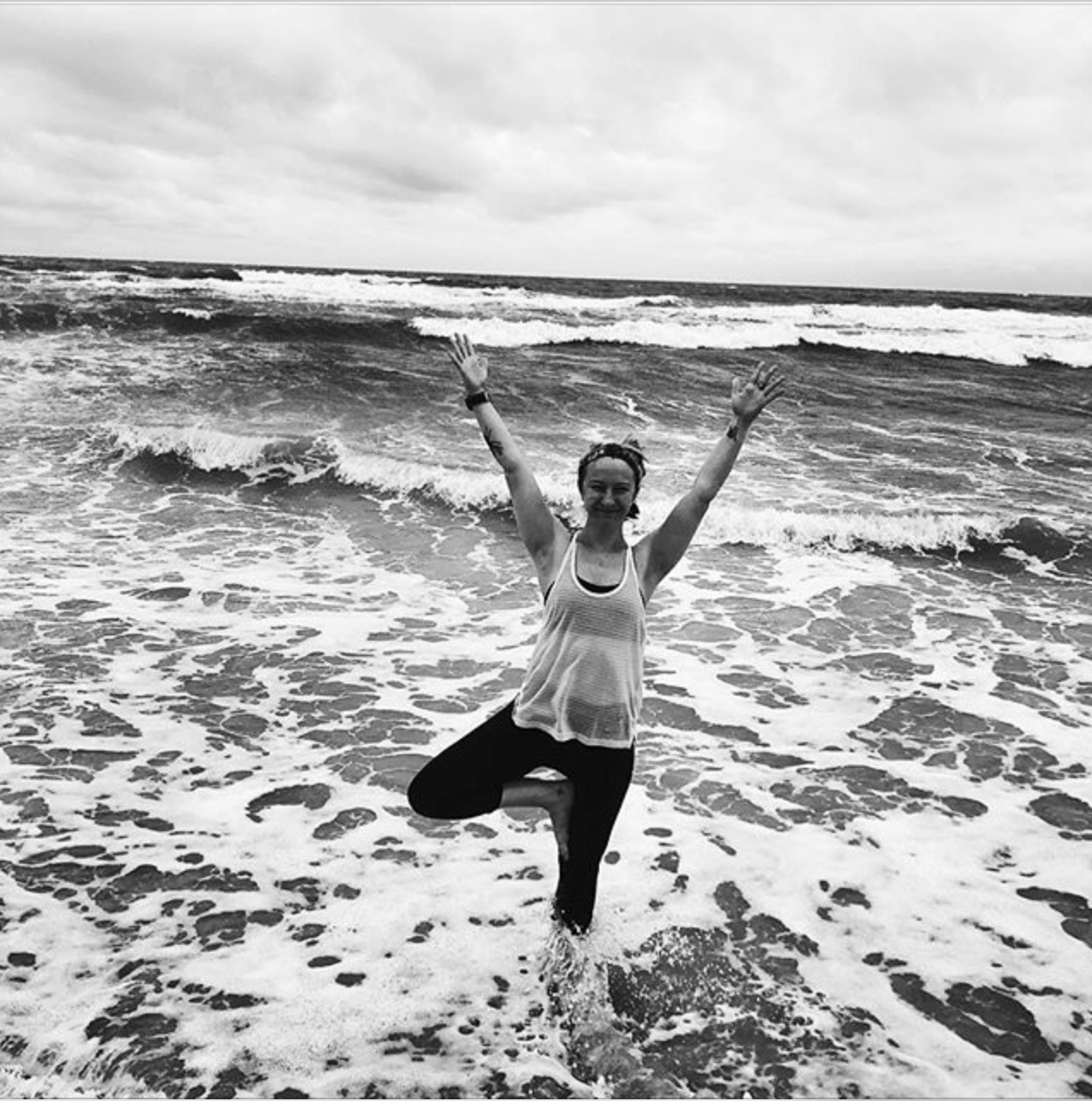 A woman does tree pose in the ocean.