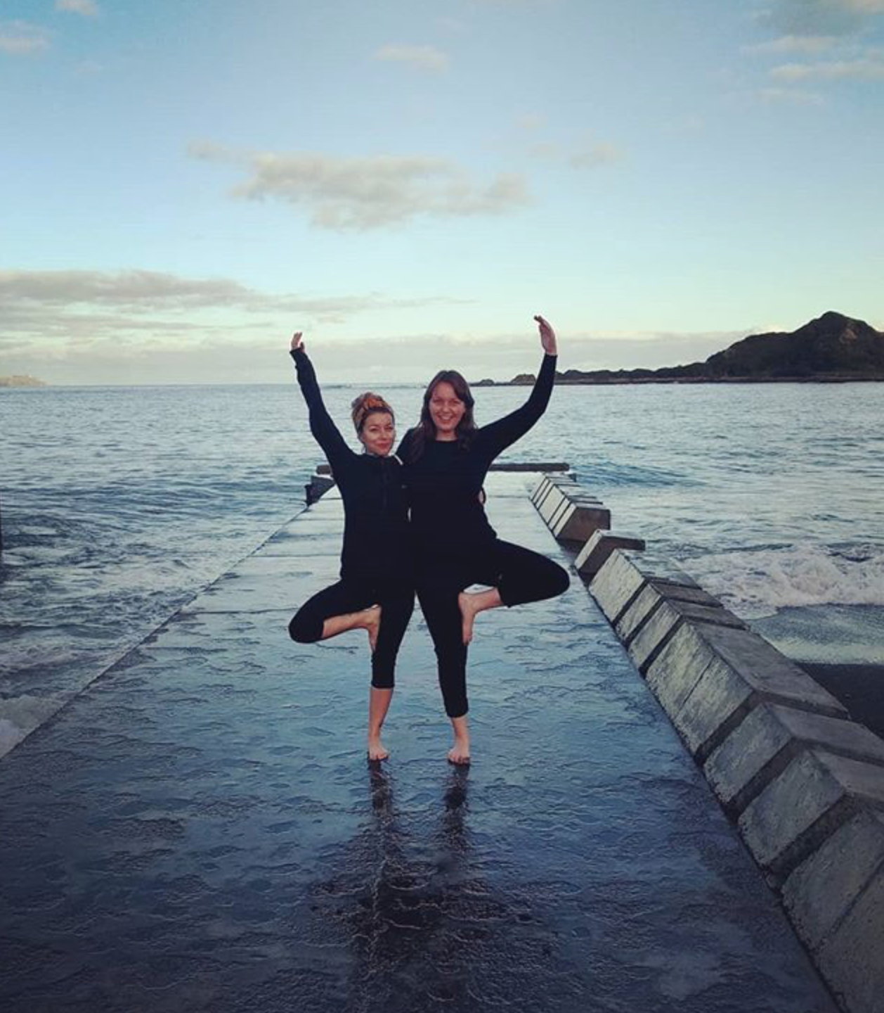 Two women hold each other as they both do tree pose on a dock by the water.