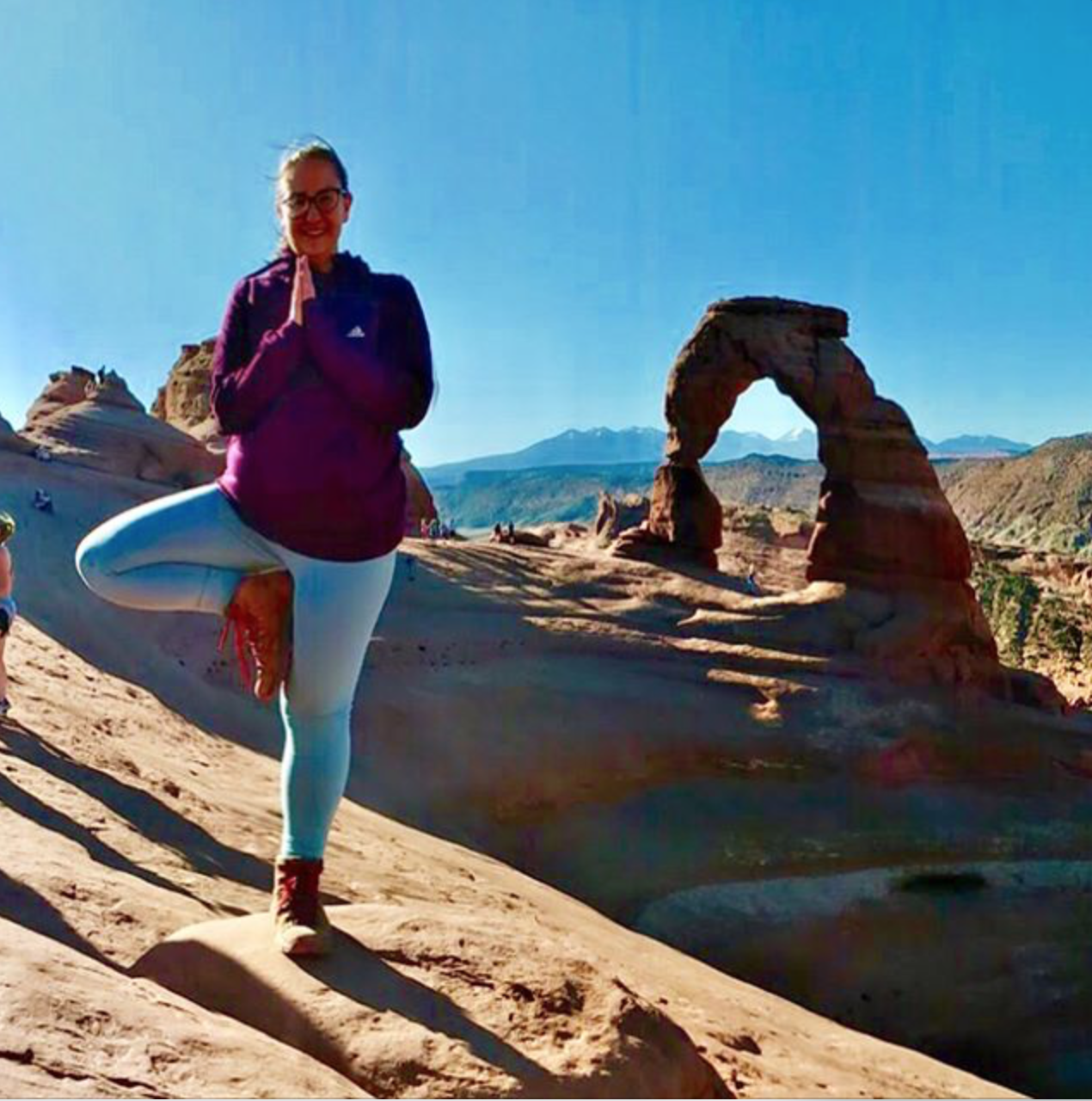 A woman does tree pose by a natural stone arch.