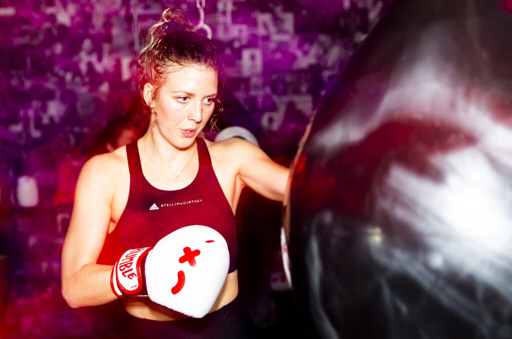 A woman jabs at a punching bag in a boxing class.