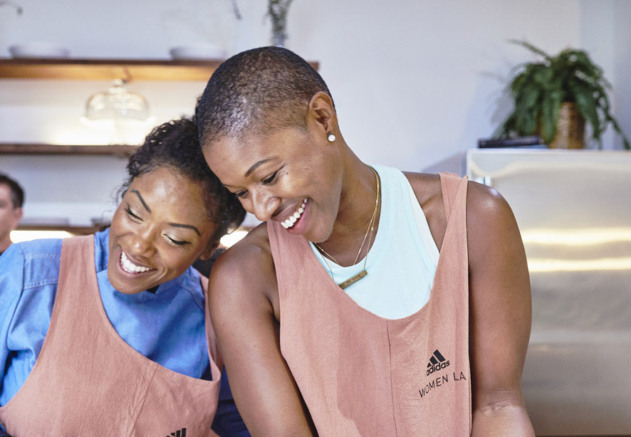 Two women lean together as they laugh.