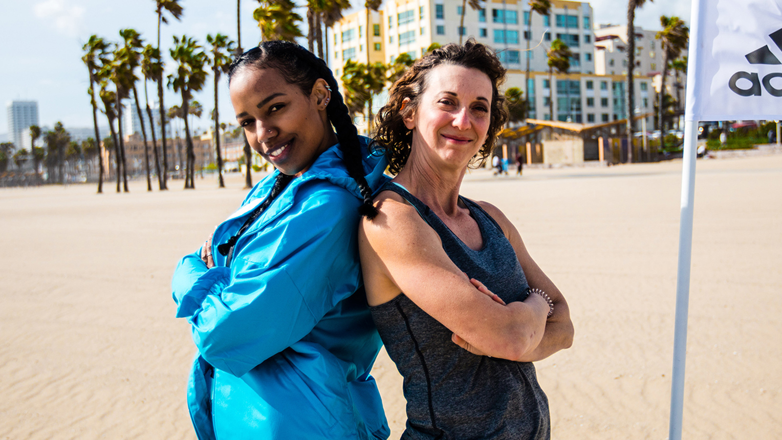 Two smiling women lean back to back, arms crossed, on a beach.