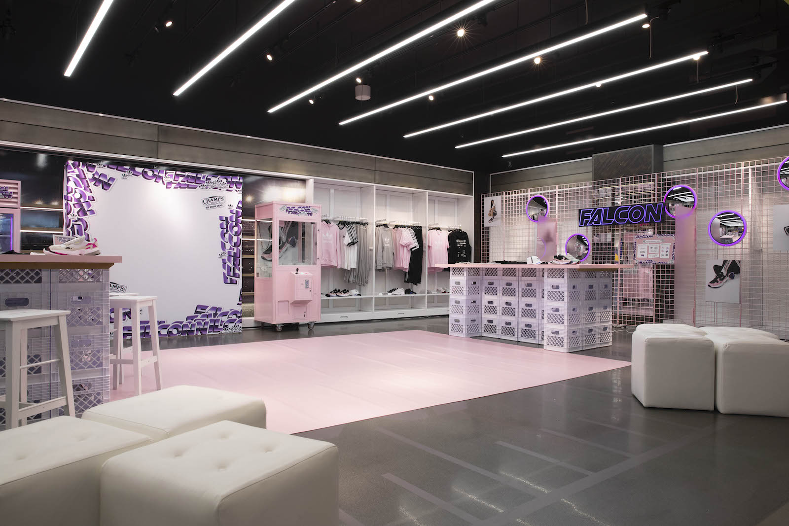 Falcon retail space with a photo op backdrop covered in large purple gradient Falcon stickers, a pink claw machine, clothing display wall , and product display counters show pairs of Falcon sneakers.