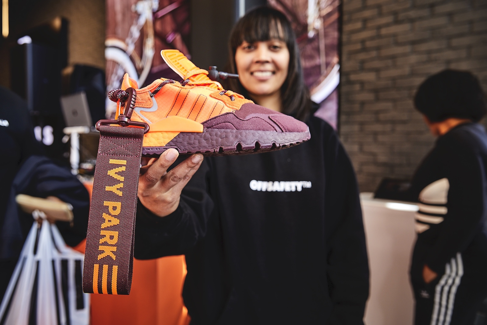 A guest holds up an orange and burgundy Ivy Park sneaker.