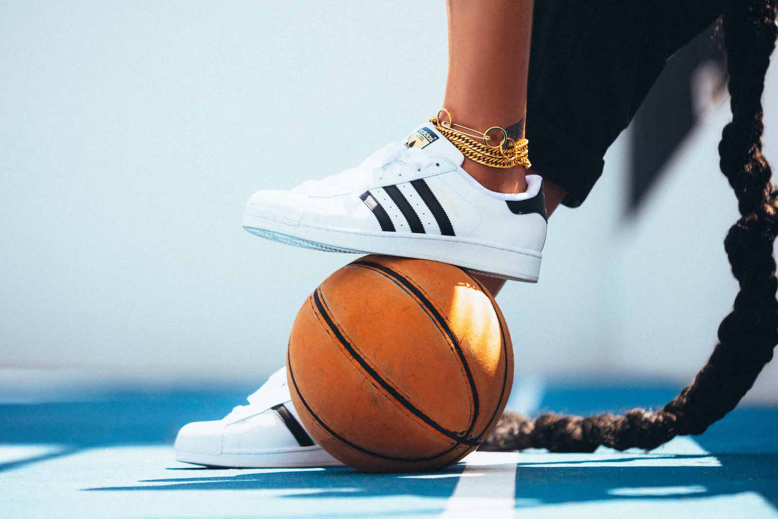 A closeup of a pair of adidas shoes on Liz Cambage, with one foot, decked out in gold anklets, resting on a basketball.