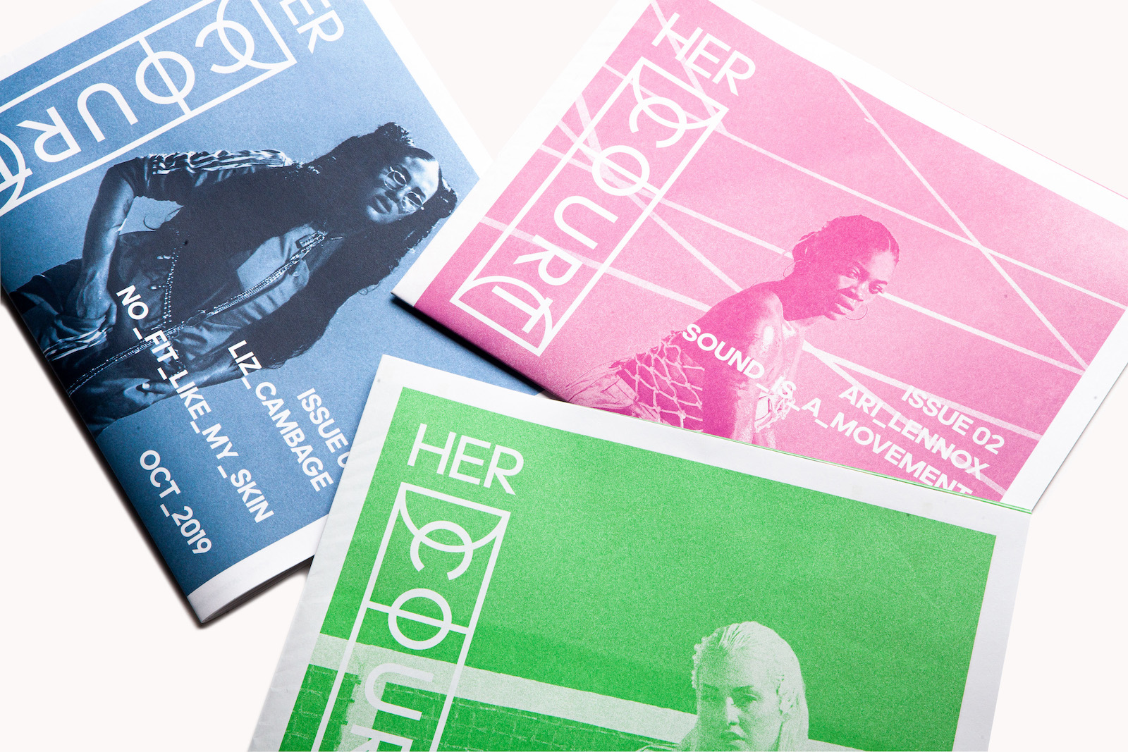 A stack of three newsprint zines, each printed in duotone: one blue, one pink and one green.