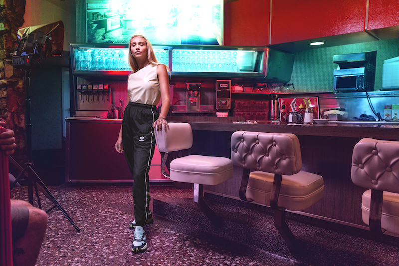 A model stands at the diner counter, hand resting on the back of a stool.