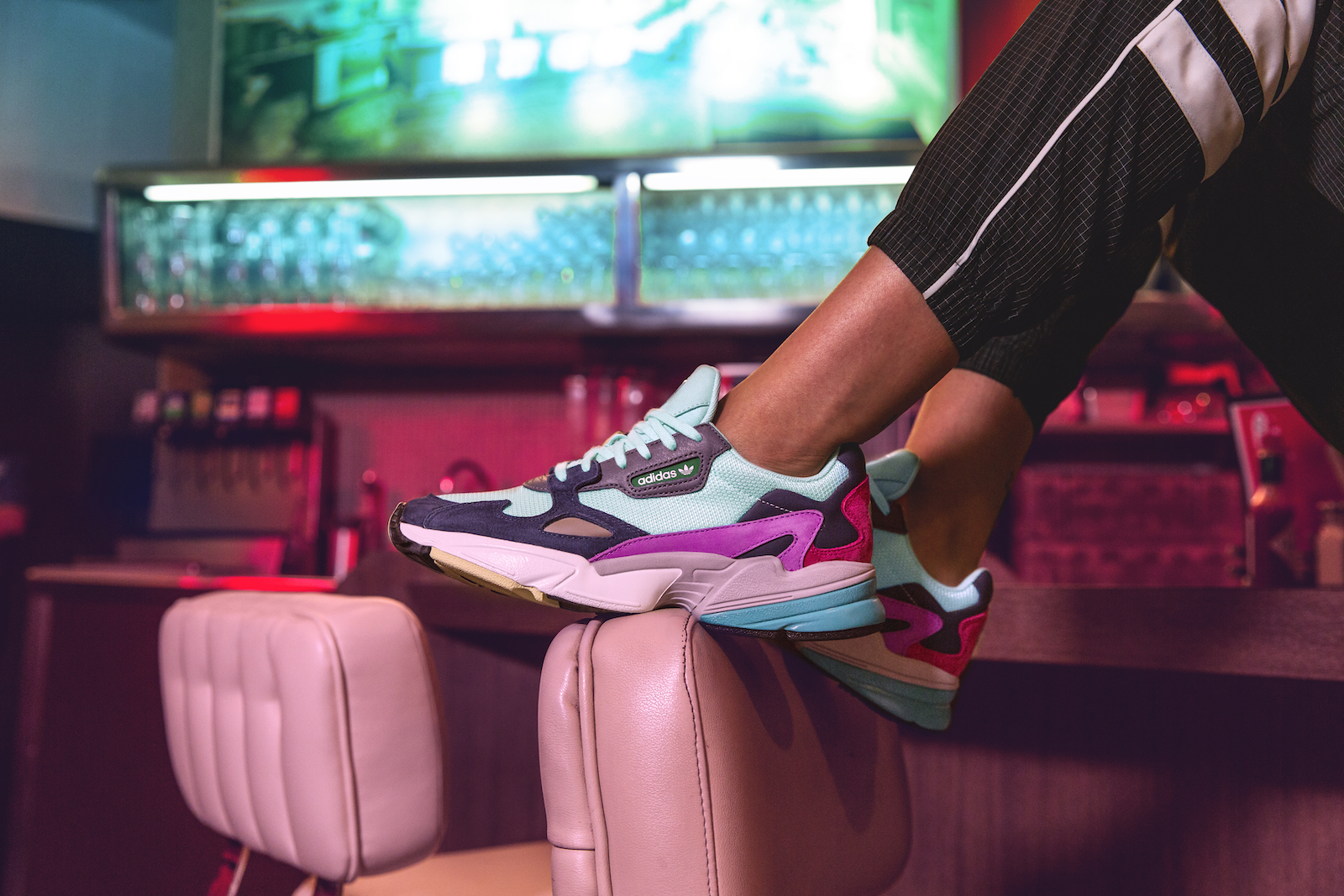 Closeup of a pair of Falcon sneakers on a model sitting on the diner counter, feet resting on the pink, leather backrest of a stool.