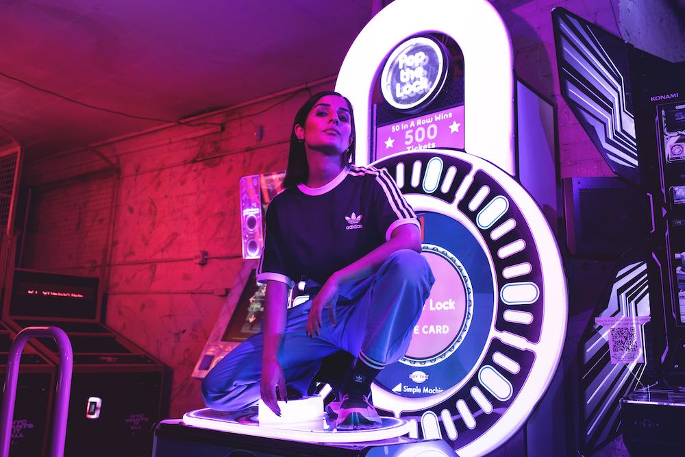 Model kneels on top of an arcade game.