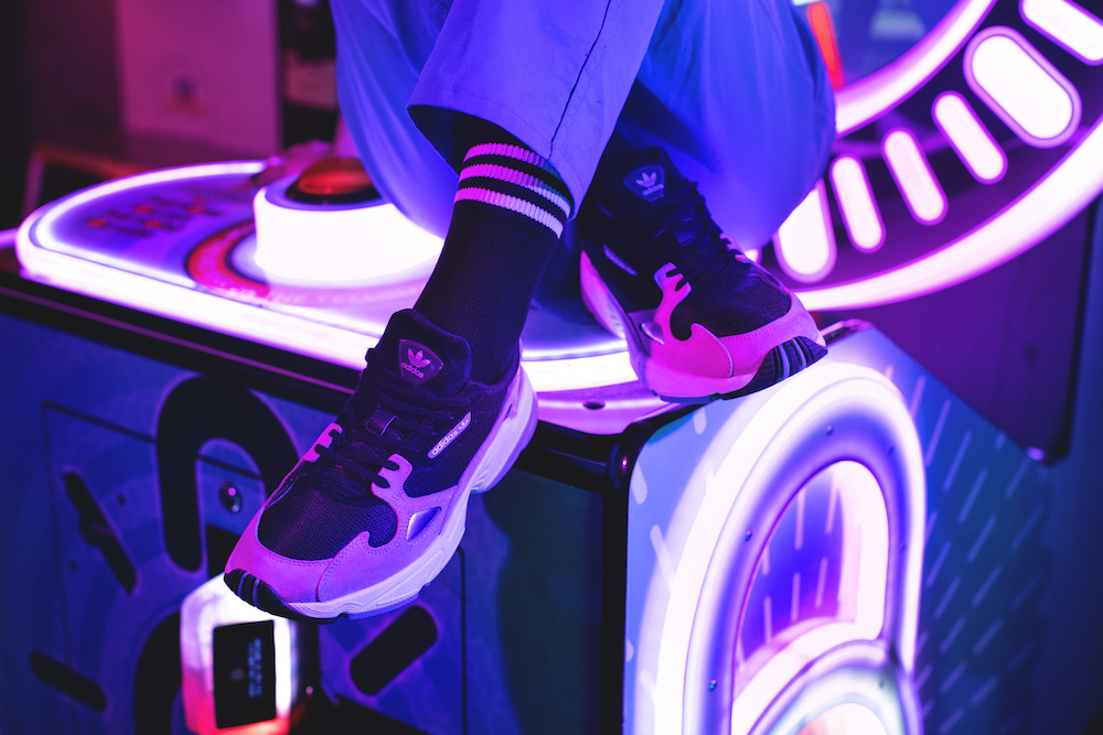Closeup of shoes on cross-legged model seated on top of an arcade game.
