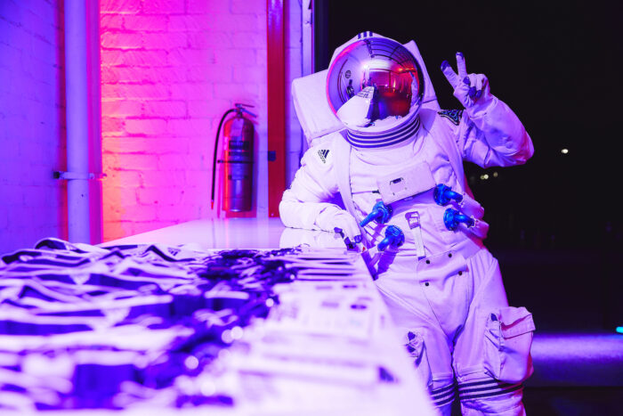 Astronaut in purple-pink light giving a peace sign while leaning on a table of event badges.