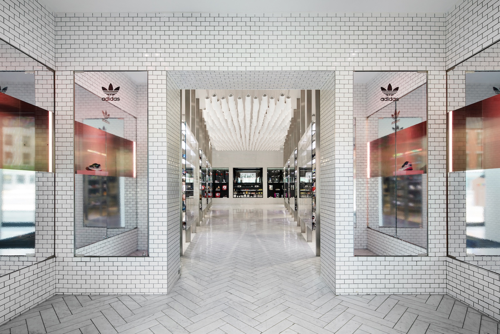 A white tiled retail space with iridescent adidas branding over mirrored surfaces and Falcon shoes in vitrine displays.
