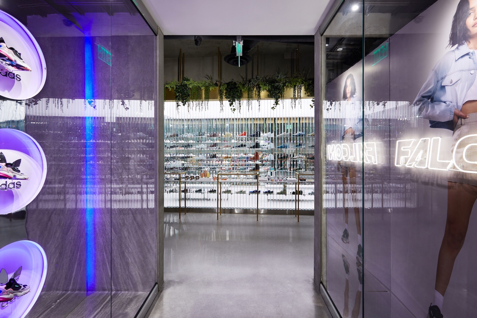 A hallway with three Falcon sneakers displayed in purple-lit circular cutouts on the left and campaign imagery with neon signs reading Falcon on the right. A wall of sneakers is at the end of the hall.