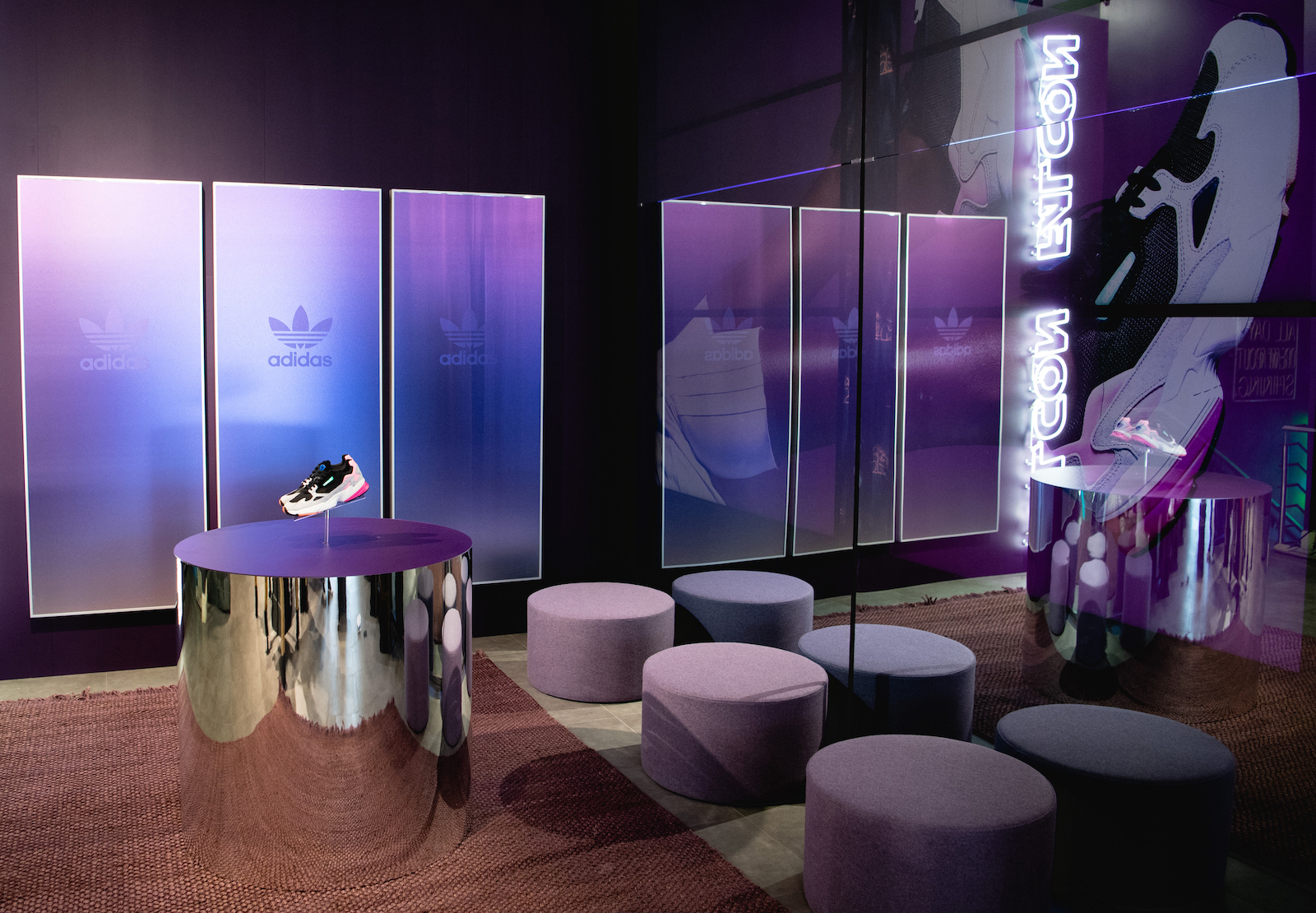 A  retail buildout with purple fogged glass, Falcon in neon, with shoes popped off a reflective cylinder pedestal.