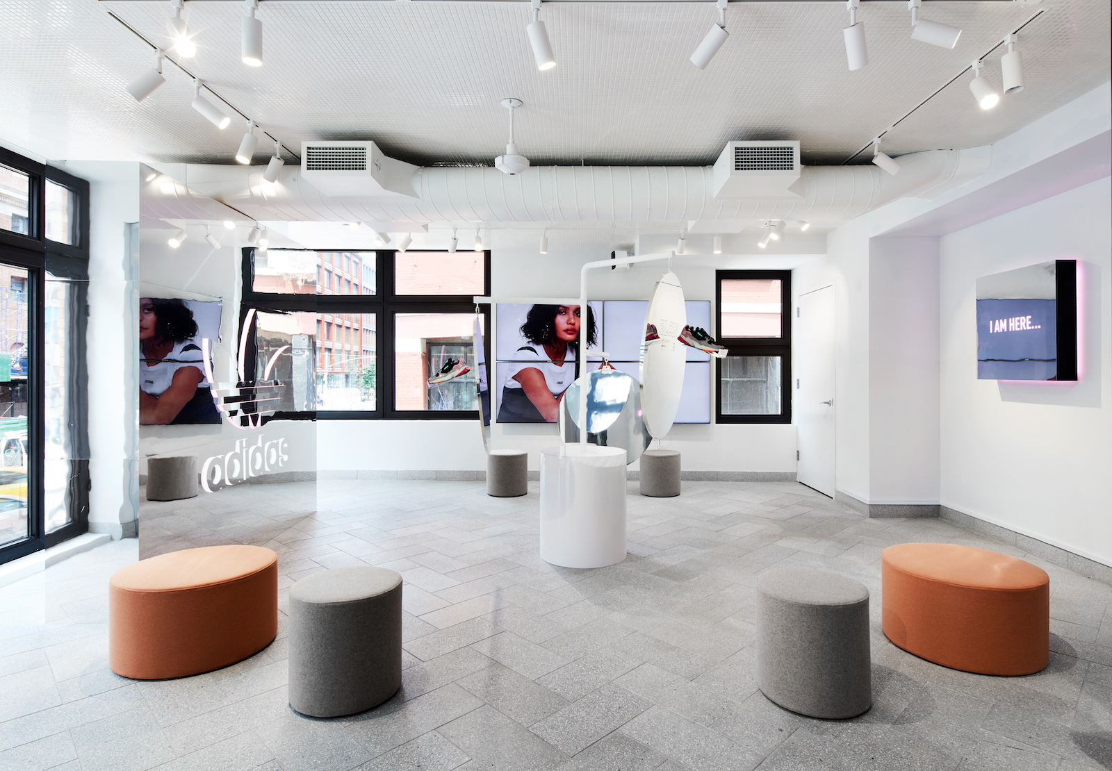 A clean, light retail space buildout with mirror elements displaying the shoe and adidas logo prominently.