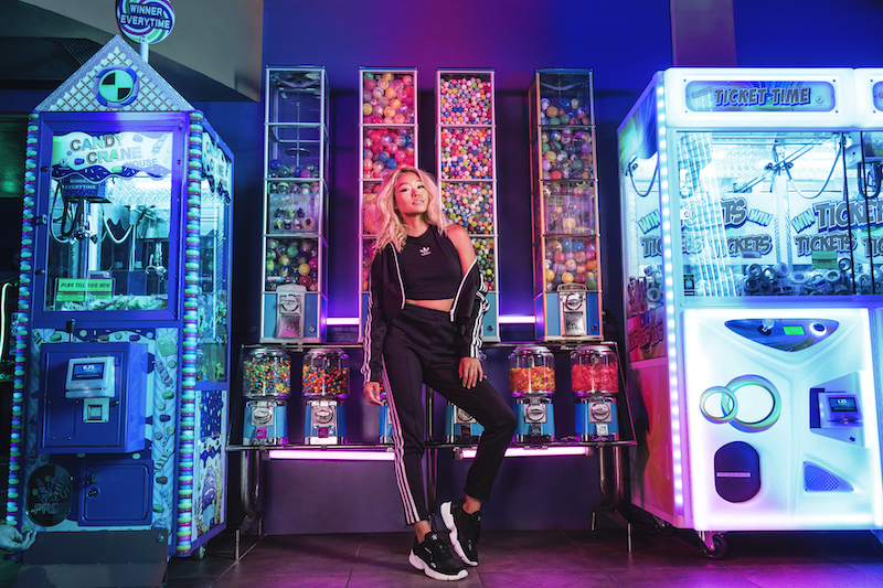 A model stands in front of a row of candy and toy vending machines.