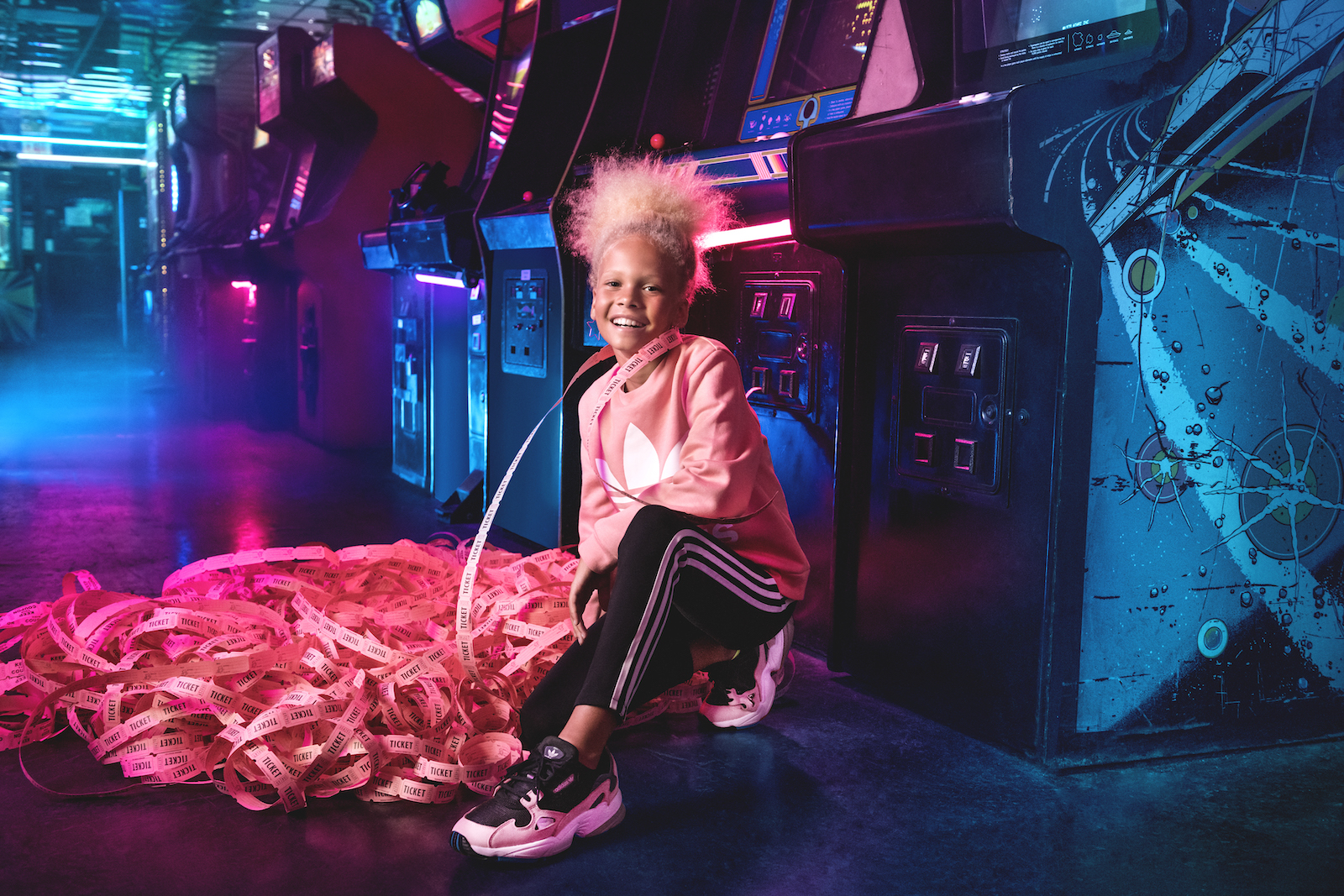 A smiling girl kneels in front of a row of arcade games with a huge pile of pink tickets.