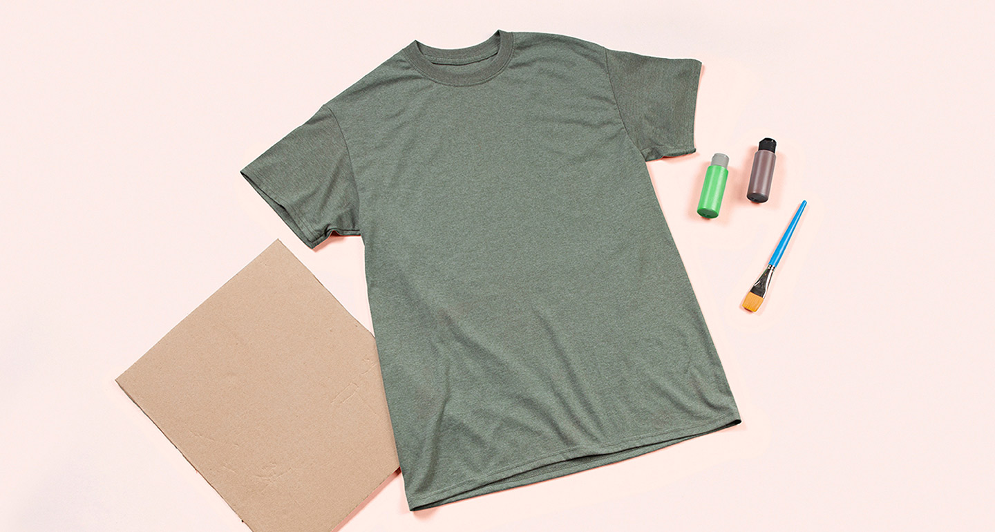 Step 1: Gather supplies: a shirt, a piece of cardboard, green and brown fabric paint, a one-inch wide flat paintbrush.