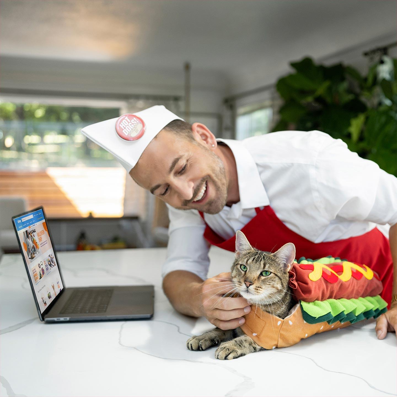 Cat in hotdog costume with owner dressed as a hotdog vendor