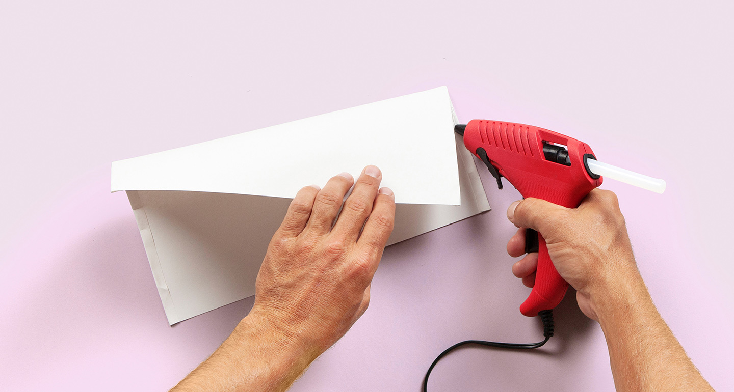 Paper being folded and glued with glue gun