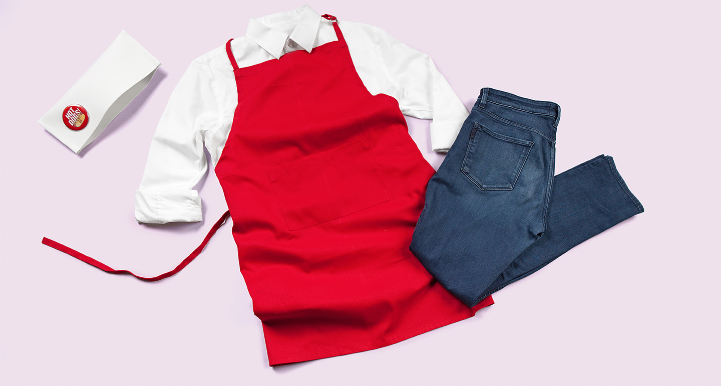 Completed hot dog vendor costume with hat, white shirt with rolled up sleeves, red apron, and blue jeans.