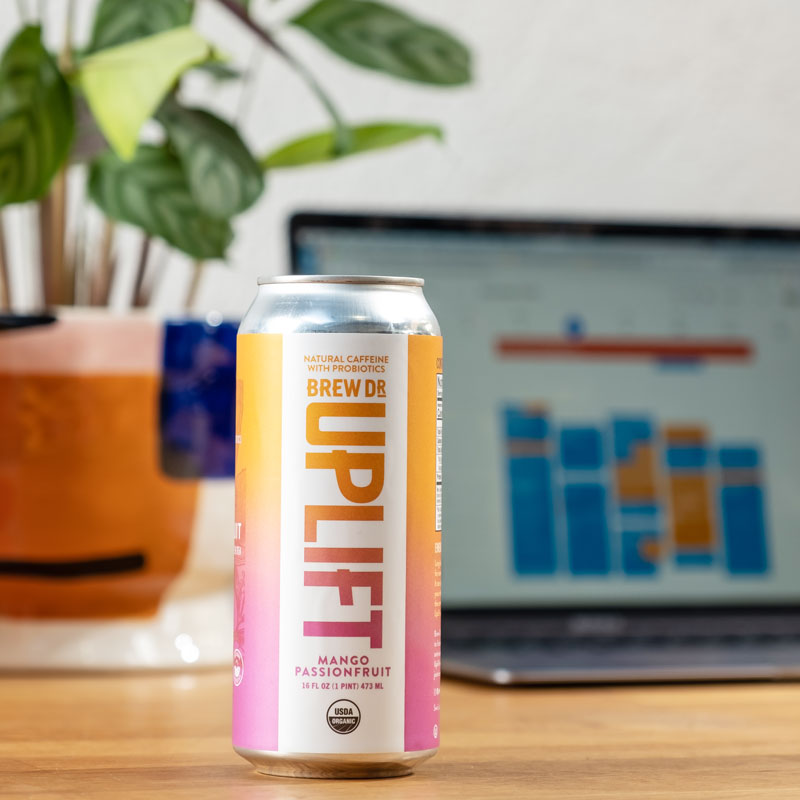 A can set on a desk by a laptop.