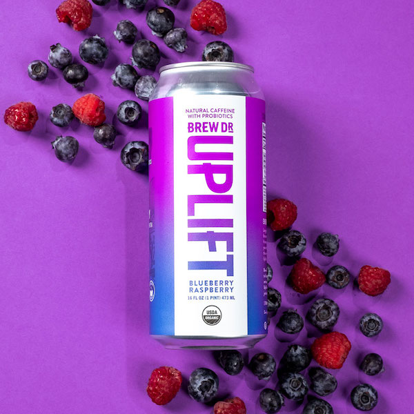 The Blueberry Raspberry Uplift can  on a purple background with a scattering of blueberries and raspberries.