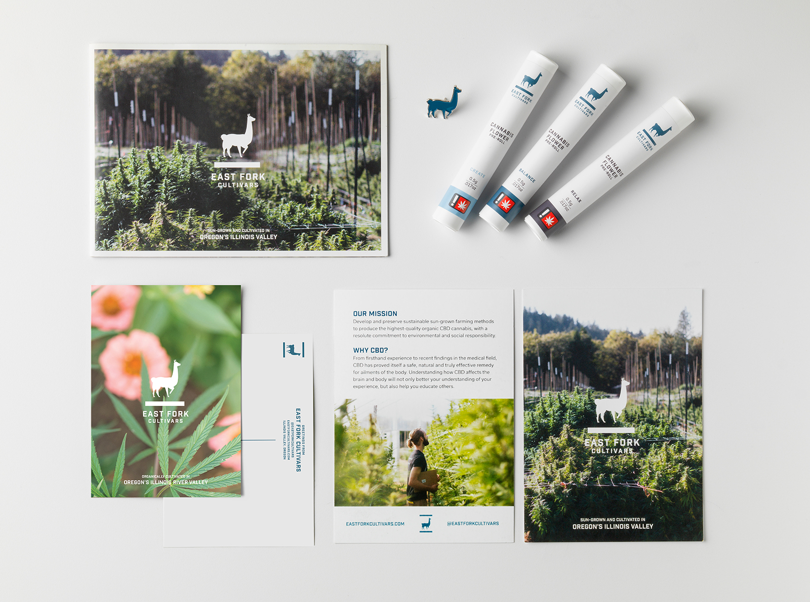 A collection of printed materials. A large card showing the plants on the farm with the white East Fork logo overtop; a blue enamel llama pin; three pre-rolls; the front and back of an informational card with a photo of the farm, stating Our Mission and Why CBD?; and the front and back of a postcard with a picture of cannabis leaves over pink flowers with the white East Fork logo overtop.