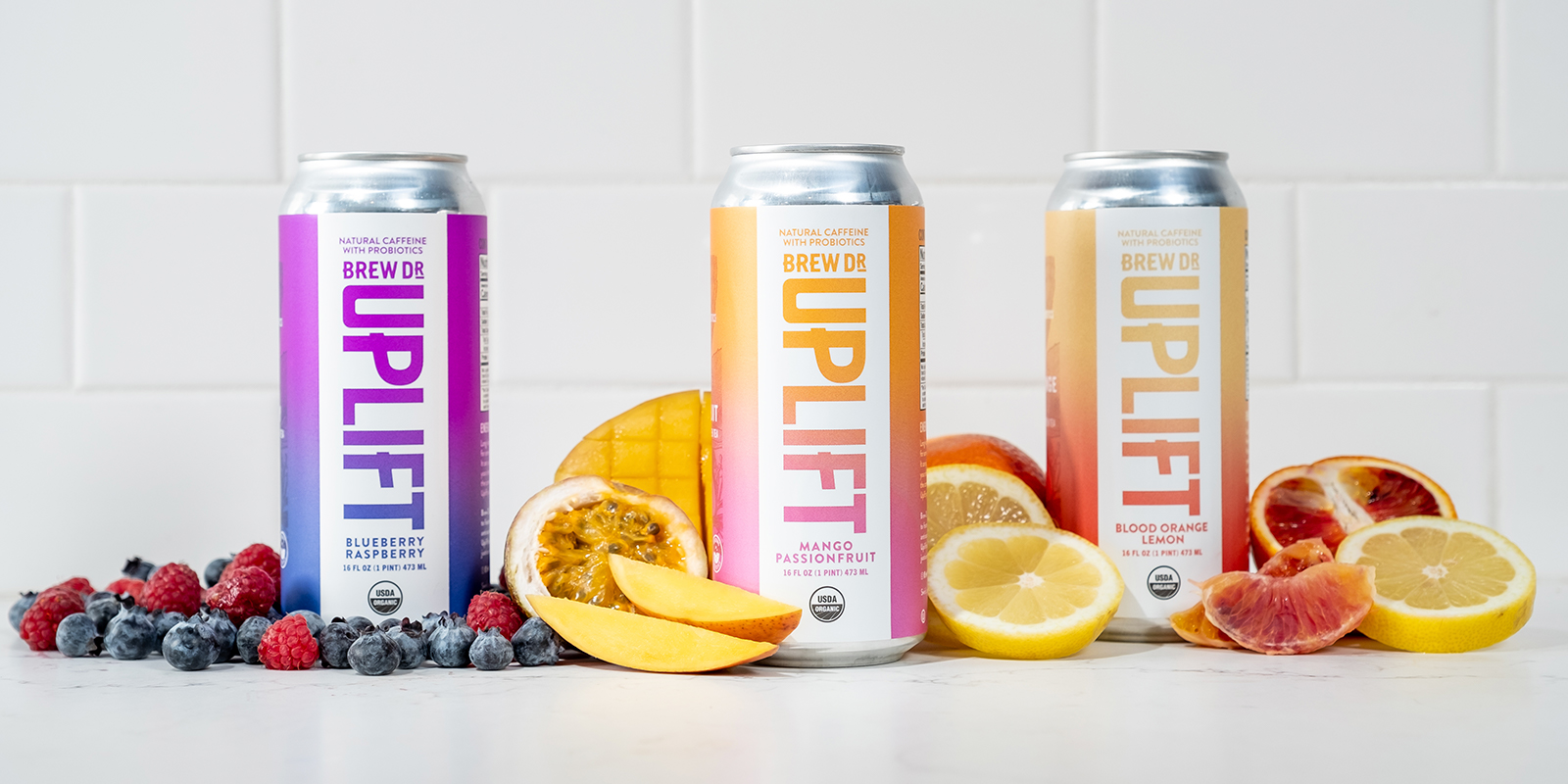 The three cans, Blueberry Raspberry, Mango Passionfruit, and Blood Orange Lemon, lined up on a counter surrounded by the fresh fruit that makes up their ingredients. Each has a white front panel with knocked-out vertical version of the Uplift logo so the gradient behind, which wraps around the whole can, shows through. The Blueberry Raspberry gradient is a dark blue to purple, the Mango Passionfruit a pink to orange, and the Blood Orange Lemon a red-orange to yellow.