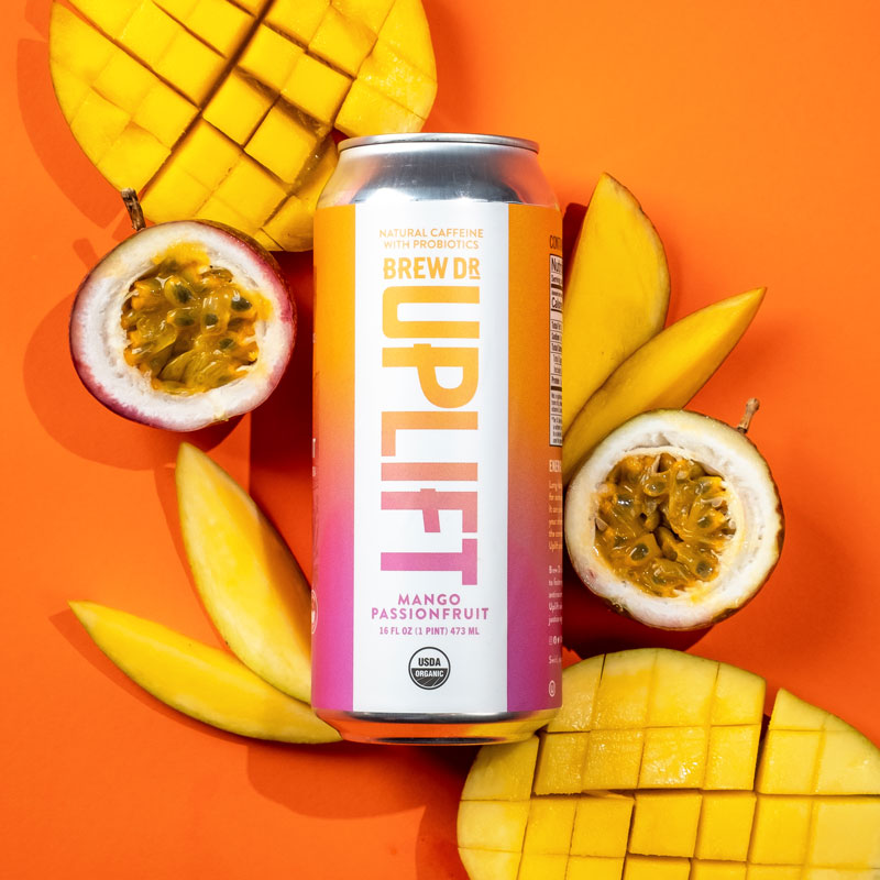 The Mango Passionfruit can on an orange background with slices of mango and a passion fruit cut in half.