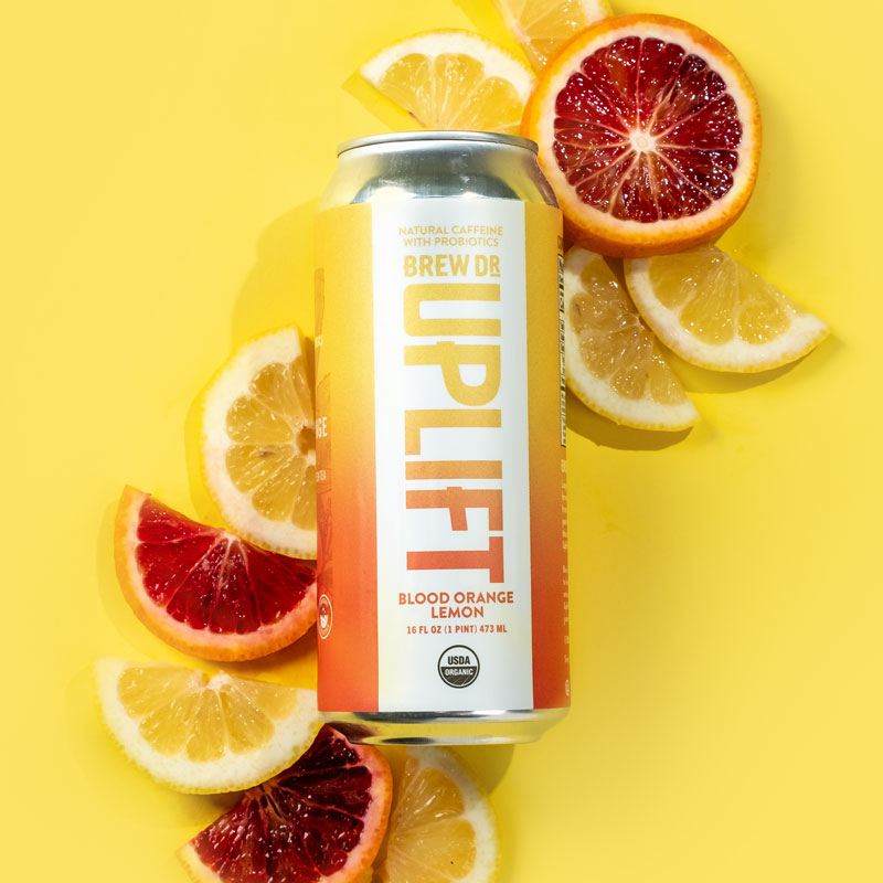 The Blood Orange Lemon can on a yellow background with slices of lemon and blood orange.