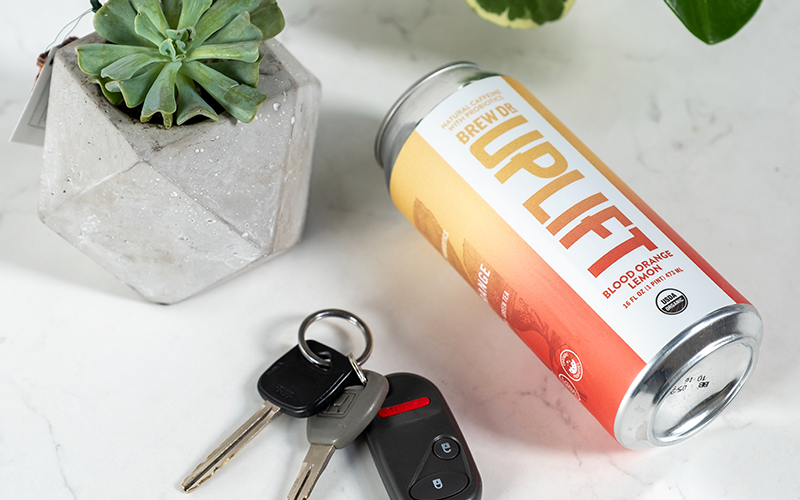 A can of Uplift laying on its side on a marble table top next to a small plant and a set of car keys.