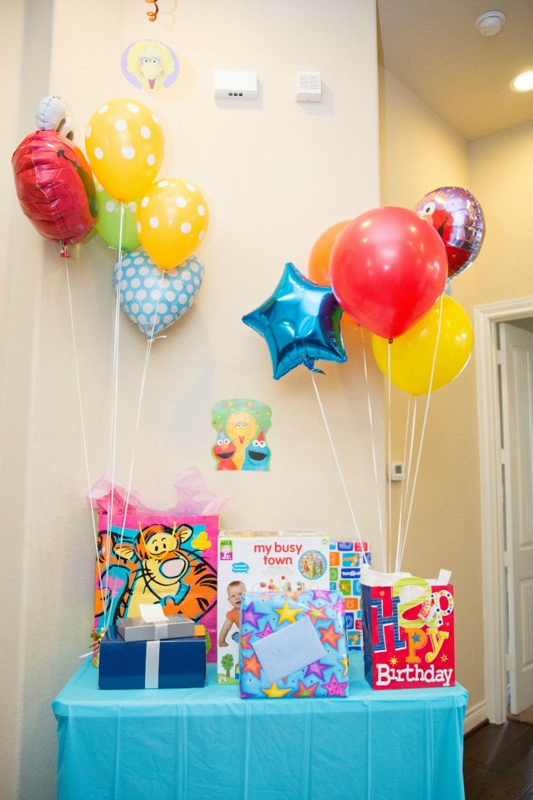 Celebrating turning one with balloons, Sesame Street, and a gift table