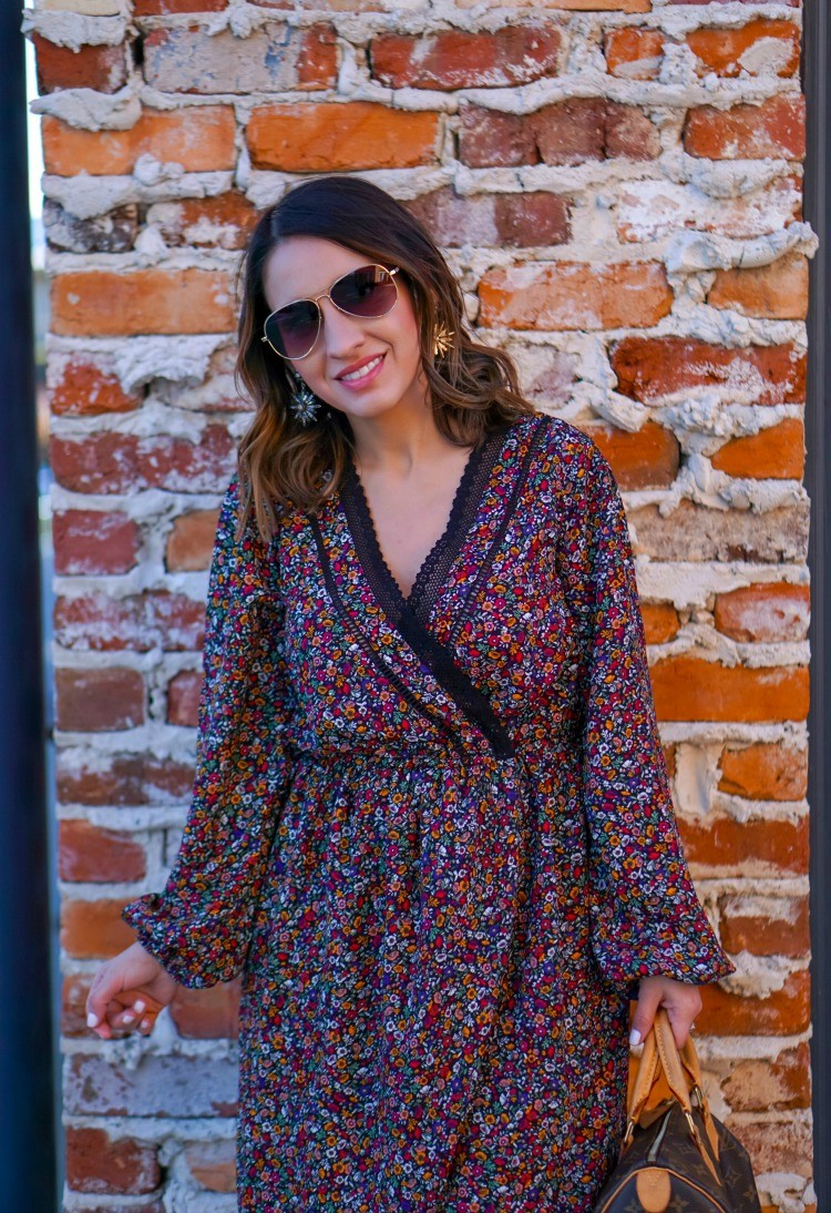 Sunglasses, floral wrap dress, and statement earrings