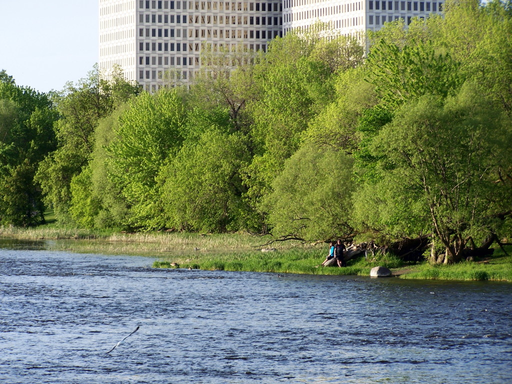 A young couple sit together on a log on the far, wooded shore of the river. Several towers loom in the distance.