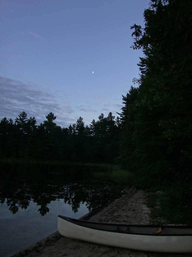 A crescent moon looks down from a deep blue twilight sky on band of dark trees and white canoe beside a still lake.