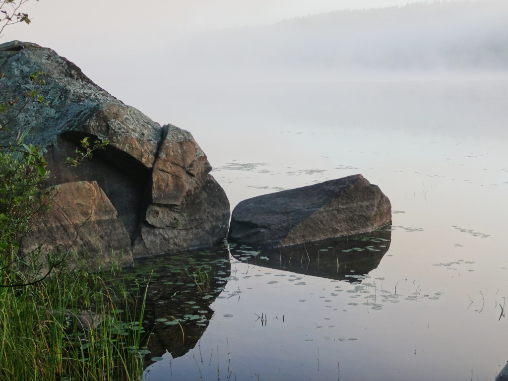 Boulders reflect in the still water of a mist covered lake in early morning light.