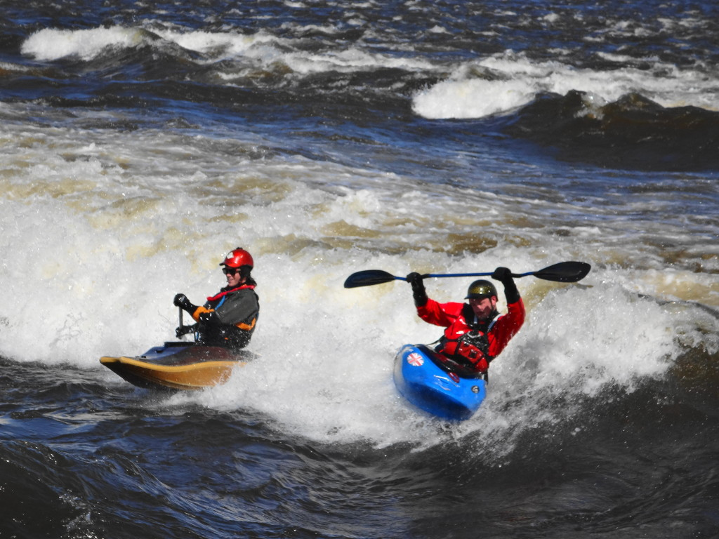 "After one of the three kayakers loses his place on ""The Wave"", the remaining two kayakers perform some tricks."