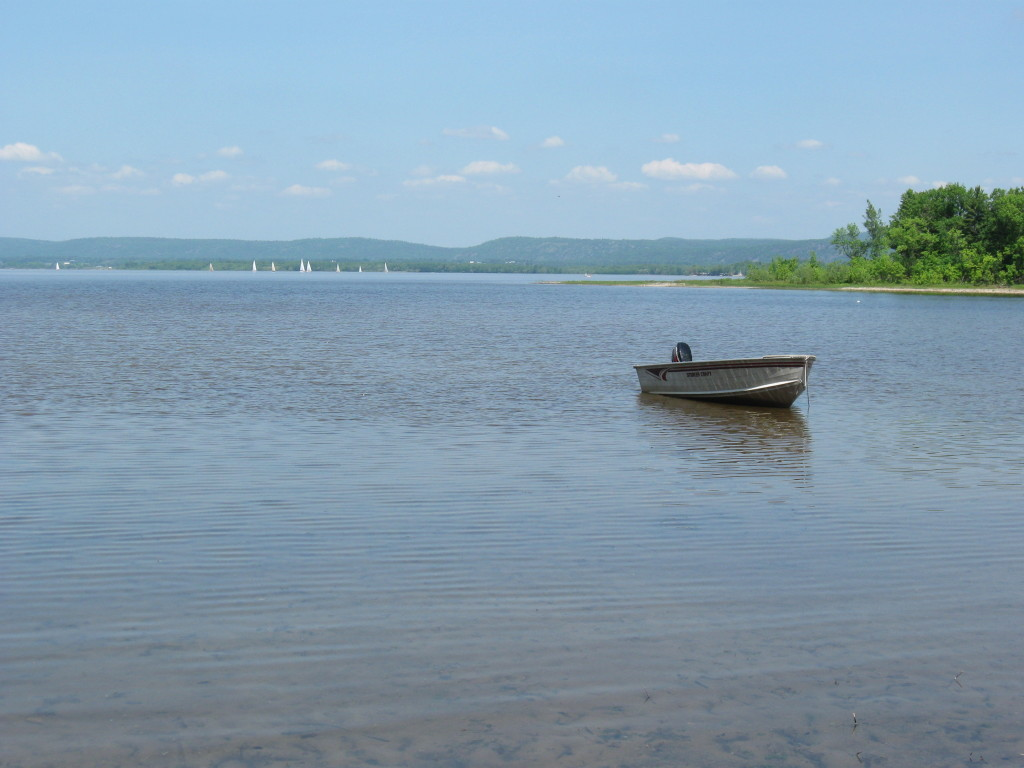An aluminum boat floats in the shallows of Constance Bay at the end of Greenland Road, with sail boats and the Quebec shoreline in the distant background.