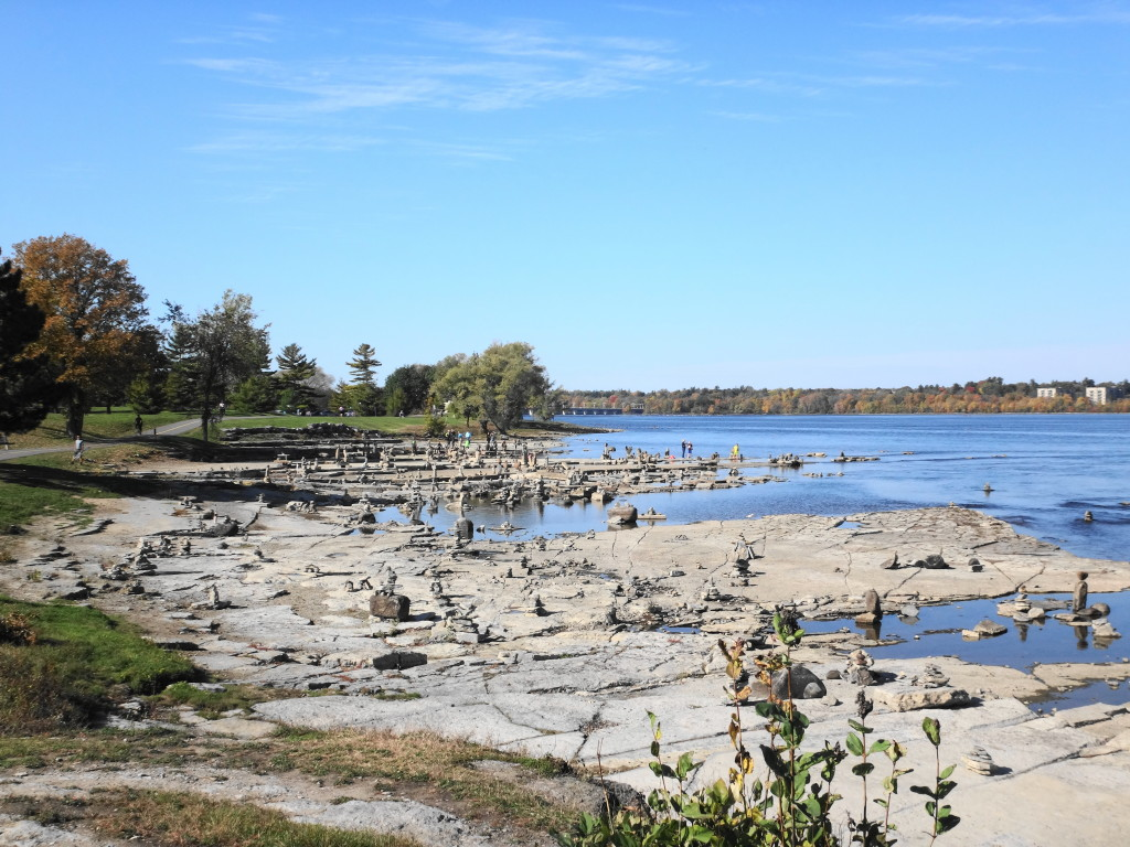 Under a beautiful, blue sky, balanced stone sculptures crowd the exposed shoreline rocks at Remic Rapids.