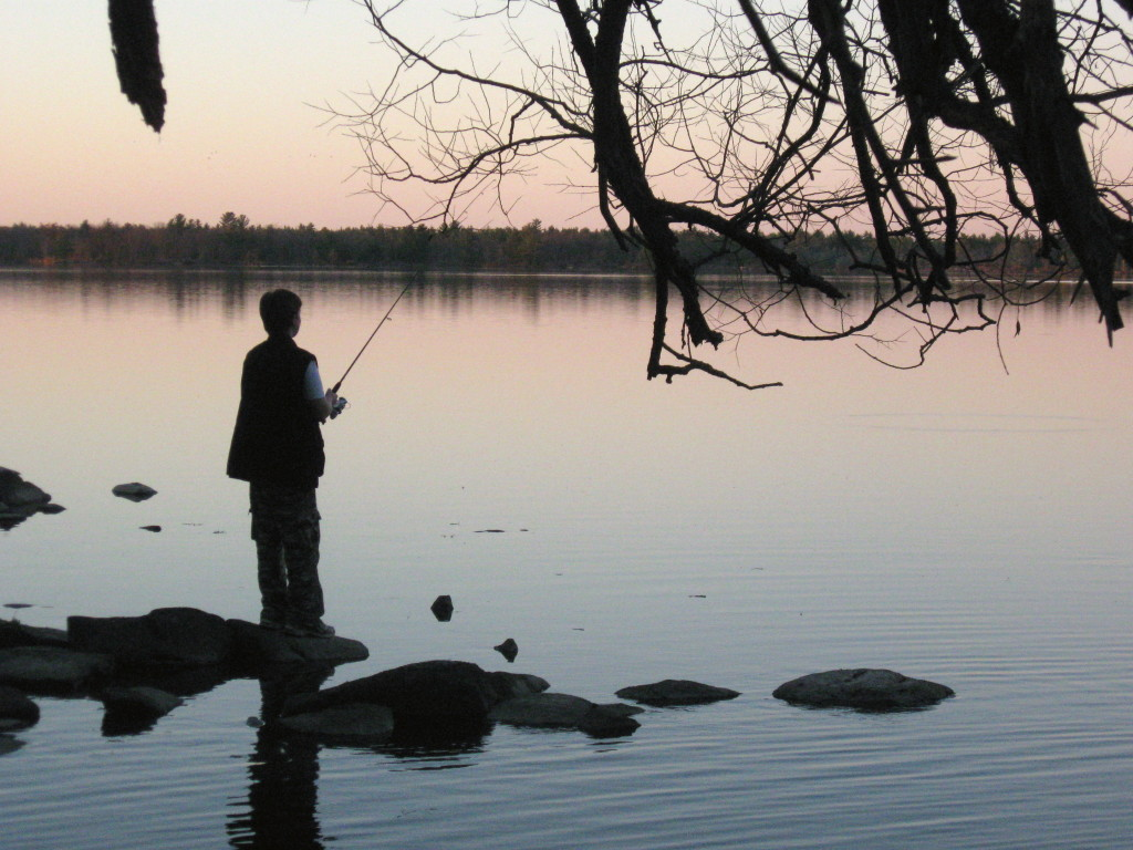 A teenage boy fishes from the shoreline, silhouetted against the river and sunset.