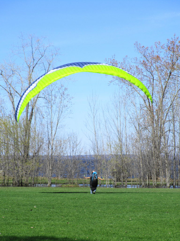 A man flys a parasail on a lawn at Britannia Park as a strong wind blows off the river.