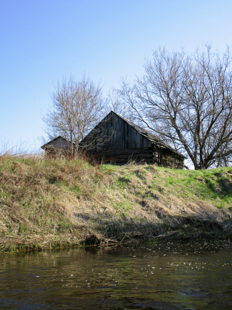 A dilapidated farm building sits on a high bank beside the Jock River.