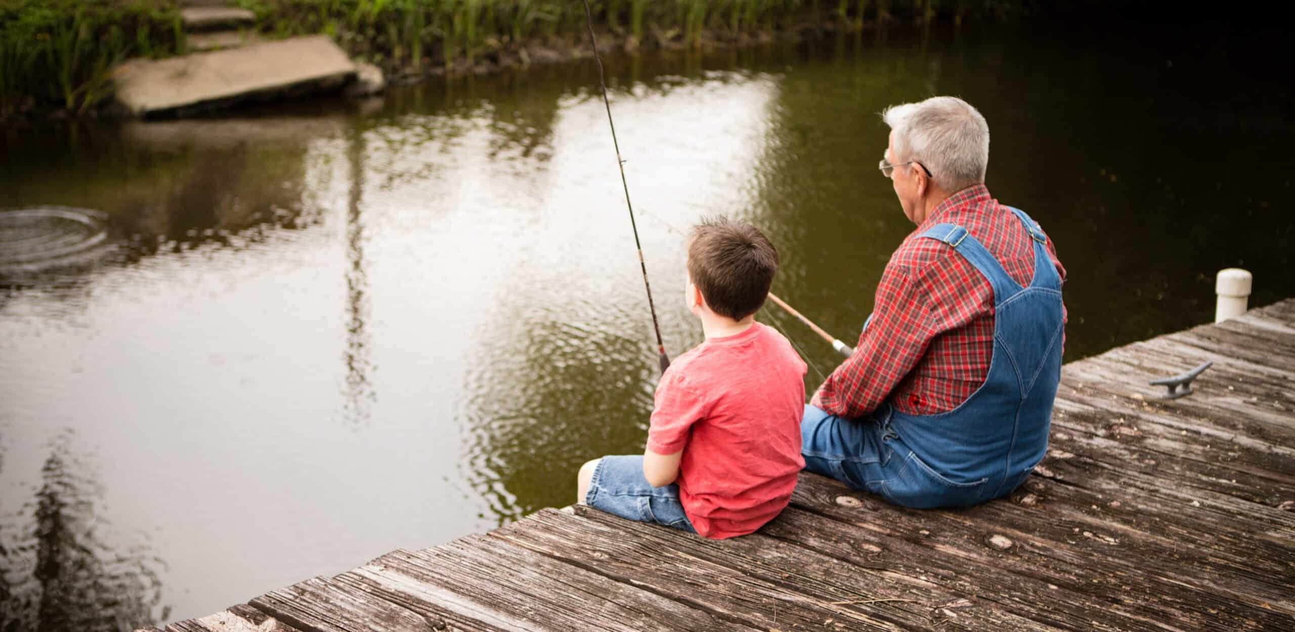 Grandfather and grandfather fishing off of a dock sharing family stories