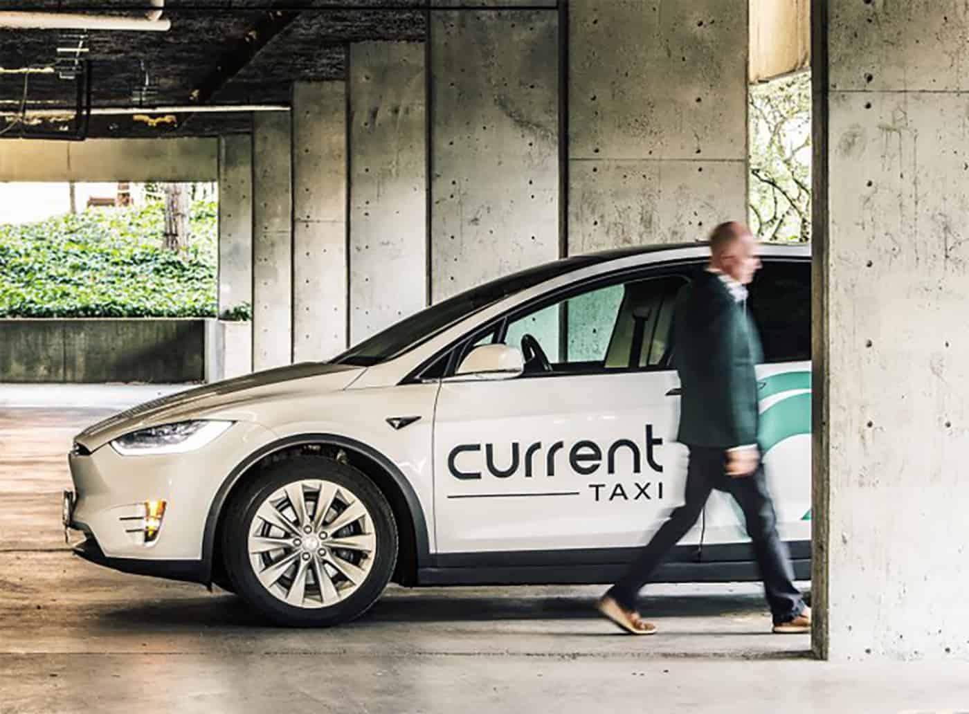 Current taxi brand ambassador walks past a parked Tesla Taxi